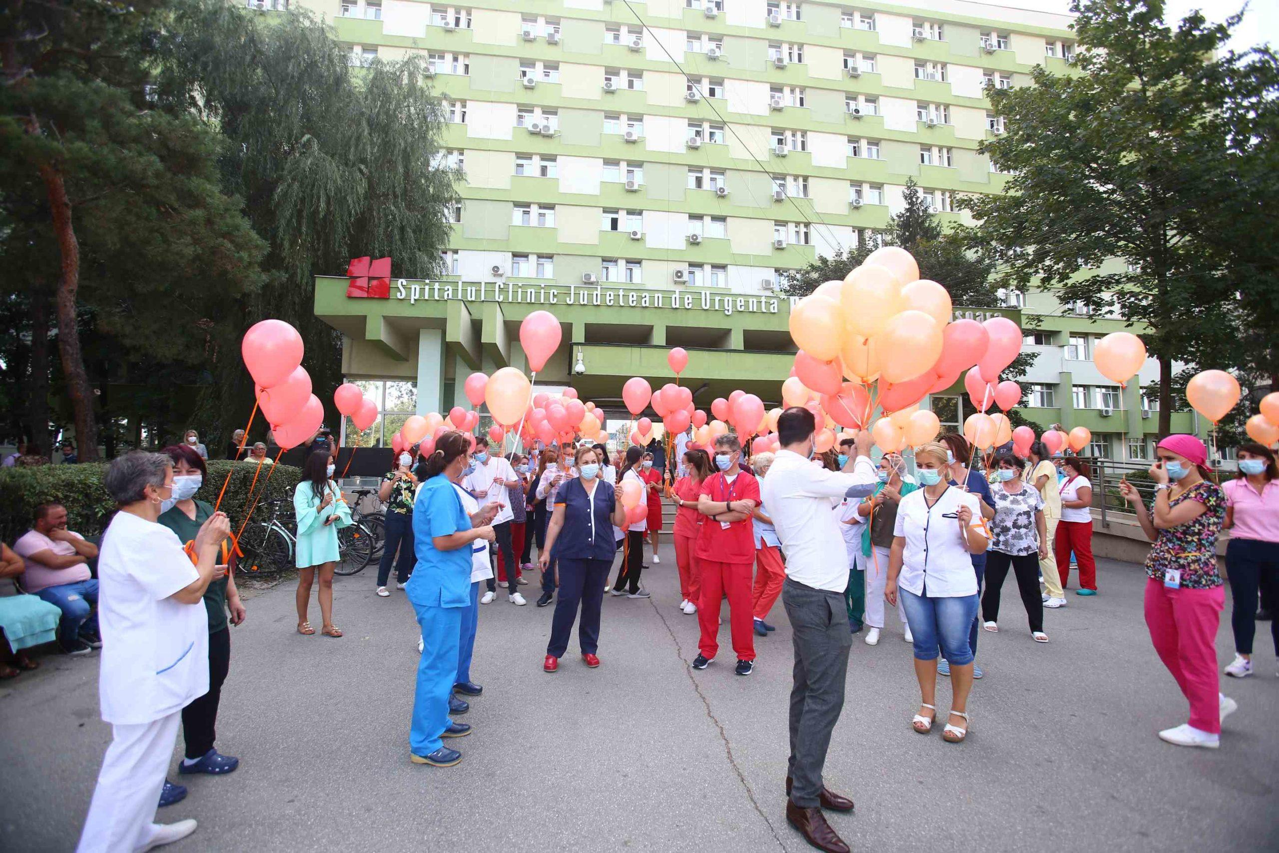 Baloane portocalii lansate în fața Spitalului Județean Timișoara pentru pacienți și aplauze pentru cadrele medicale aflate în lupta cu Covid-19